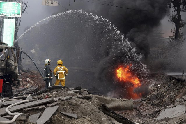 Firemen put out fire on the part of a destroyed street as fire continue to burn following multiple explosions from an underground gas leak in Kaohsiung, Taiwan, early Friday, August 1, 2014. (Photo by AP Photo)