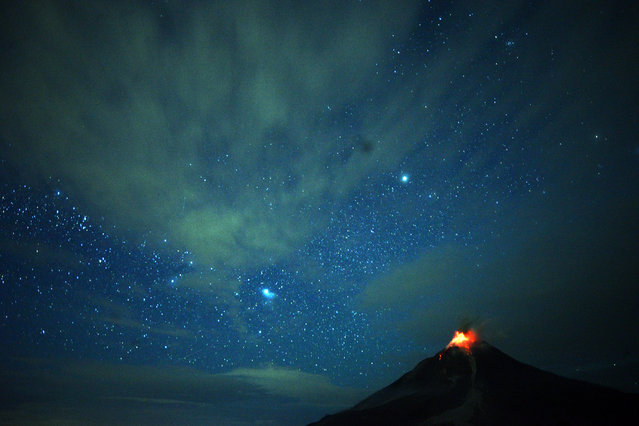 This timed-exposure photo taken on December 28, 2017 shows Moung Sinabung volcano spewing lava that lights up the night sky in Karo, North Sumatra. Mount Sinabung roared back to life in 2010 for the first time in 400 years, after another period of inactivity it erupted once more in 2013, and has remained highly active since. (Photo by Lana Priatna/AFP Photo)