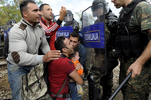 Migrants confront Macedonian police during clashes at the Greek-Macedonian border, August 21, 2015. Macedonian police drove back crowds of migrants and refugees trying to enter from Greece on Friday after a night spent stranded in no-man's land by an emergency decree effectively sealing the Macedonian frontier. A Reuters reporter said tear gas was fired and saw at least four bloodied migrants taken for treatment on the Greek side of the border. (Photo by Alexandros Avramidis/Reuters)