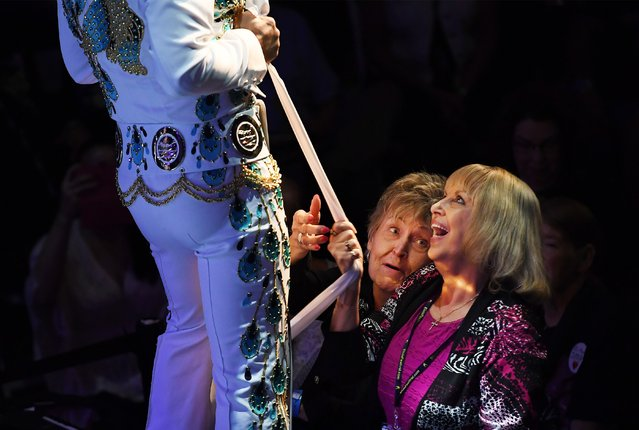 """Linda Erwin, right, of Spartanburg, S.C., tries to secure a scarf from an Elvis tribute artist, Diogo """"Di"""" Light, during the Images of the King World Championship at the New Daisy Theatre in Memphis, US on August 14, 2017. (Photo by Matt McClain/The Washington Post)"""