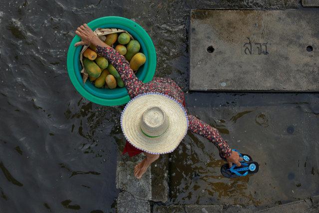 A woman carrying a basket of papayas while walking through a vegetable market in Bangkok, Thailand November 11, 2011. (Photo by Kerek Wongsa/Reuters)