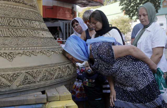 Ukrainian people kiss the new bell and pray near it, before it is lifted into place, set in the main bell tower of the golden domed Orthodox Monastery of Caves in Kiev, Ukraine, Tuesday, Aug. 19, 2014. The bell weighs 7,150 kilograms and is decorated with a unique decor, made in Ukraine. (Photo by Efrem Lukatsky/AP Photo)