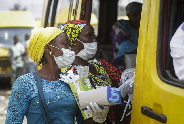 Women sell face masks and gloves, to prevent the spread of the new coronavirus, to passengers at a public minibus station in Lagos, Nigeria Friday, March 27, 2020. (Photo by Sunday Alamba/AP Photo)