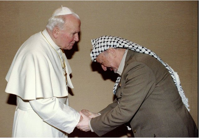 Pope John Paul II, left, greets PLO leader Yasser Arafat at his summer residence in Castelgandolfo  Saturday September 2 1995. Arafat is in Italy for talks with Italian leaders and the Israeli Foreign Minister Shimon  Peres. (Photo by Luciano Mellace/AP Photo)