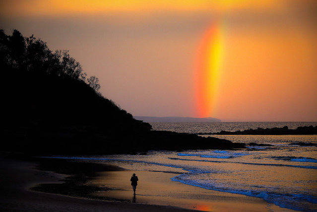 This pictures taken on April 10, 2020 shows a lone beachgoer walking on Narrawallee Beach in Mollymook, Australia as rainbow appear on the sky at the sunset. Authorities have imposed strict social distancing in place in an effort to deal with the coronavirus pandemic during Easter holidays. (Photo by David Gray/AFP Photo)