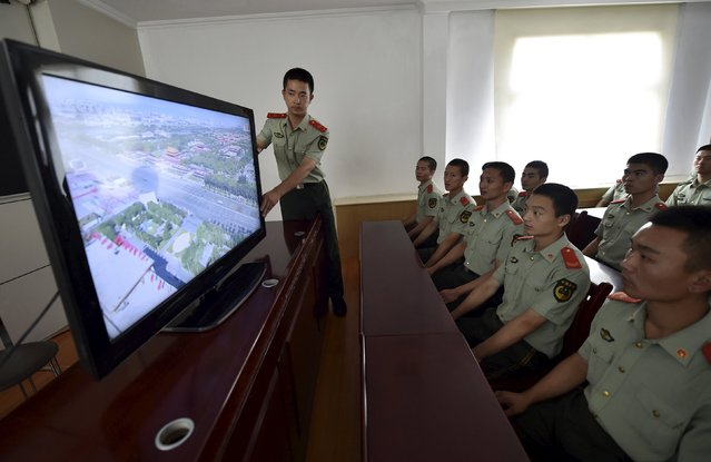 A paramilitary policeman adjusts a television set as he and his comrades look at a live broadcast of a military parade marking the 70th anniversary of the end of World War Two, at a paramilitary policemen base in Hefei, Anhui province, China, September 3, 2015. (Photo by Reuters/Stringer)
