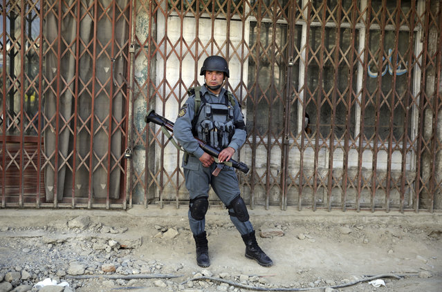 A police man stands guard at the site of a suicide attack outside a Shiite mosque in Kabul, Afghanistan, Friday, September 29, 2017. A suicide bomber blew himself up outside a Shiite mosque in the Afghan capital Kabul on Friday, killing four people and wounding 20 others, authorities said. (Photo by Massoud Hossaini/AP Photo)