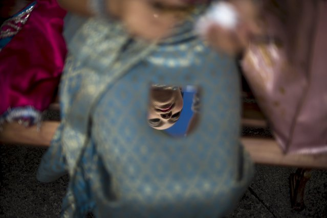 A traditional Thai dancer is seen reflected in a mirror as she touches up her makeup before a religious ceremony at the Erawan shrine, the site of a recent deadly blast and now repaired, in central Bangkok, Thailand, September 4, 2015. (Photo by Athit Perawongmetha/Reuters)