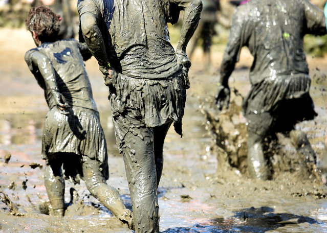 """Participants leave the pitch after their match at the so called """"Wattoluempiade"""" (Mud Olympics) in Brunsbuettel at the North Sea, Germany July 30, 2016. (Photo by Fabian Bimmer/Reuters)"""