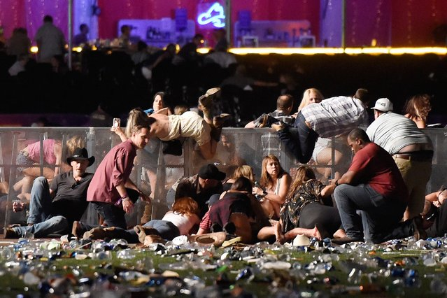 People scramble for shelter at the Route 91 Harvest country music festival after apparent gun fire was heard on October 1, 2017 in Las Vegas, Nevada. A gunman has opened fire on a music festival in Las Vegas, leaving at least 20 people dead and more than 100 injured. Police have confirmed that one suspect has been shot. The investigation is ongoing. (Photo by David Becker/Getty Images)