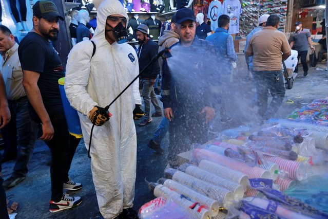 A civil defense worker wearing a protective suit sprays disinfectant as a precaution against the new coronavirus, in the main market, Baghdad, Iraq, Tuesday, March 10, 2020. For most people, the new coronavirus causes only mild or moderate symptoms, such as fever and cough. For some, especially older adults and people with existing health problems, it can cause more severe illness, including pneumonia. (Photo by Hadi Mizban/AP Photo)
