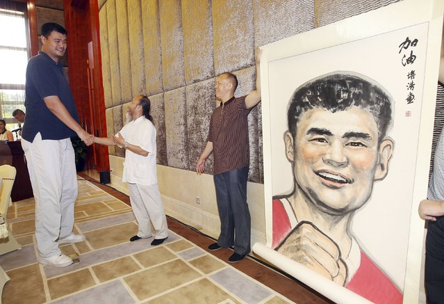 Former NBA basketball player Yao Ming (L) shakes hands with a Chinese artist as he receives a portrait of himself ahead of a charity basketball game organized by Yao Foundation, in Dongguan, August 31, 2014. (Photo by Reuters/Stringer)