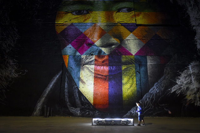 "A child plays in front of ""Etnias"", a large graffiti wall by Brazilian graffiti artist Eduardo Kobra created ahead of the Rio 2016 Olympic Games at Porto Maravilha in Rio de Janeiro, Brazil, 30 July 2016. The Olympics start on 05 August. Eduardo Kobra hopes to set a Guinness World Record for the largest graffiti created by a single artist. (Photo by Lukas Coch/EPA)"