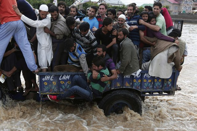 Kashmiri people hold a man as he falls from a tractor evacuating flood victims to higher grounds, as they move through a flooded street in Srinagar September 9, 2014. The prime ministers of India and Pakistan have offered to help each other in efforts to alleviate flood havoc in the disputed Himalayan region of Kashmir, lowering tension between the rival nations after weeks of army clashes and heated rhetoric. (Photo by Adnan Abidi/Reuters)
