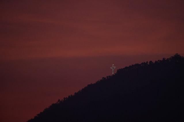 "The ""Cruz del Avila"" shines on one of the peaks of El Avila at sunset during Holy Week in Caracas, Venezuela, Wednesday, April 8, 2020. (Photo by Matias Delacroix/AP Photo)"