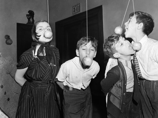 One of the games played at every Halloween party is eating, or rather, trying to eat apple suspended on a string with your hand behind you. They were few of the children of New York's Little  Italy who were guests at the Annual Halloween Party sponsored by the Children's Aid Society in New York, October 25, 1939. (Photo by AP Photo)