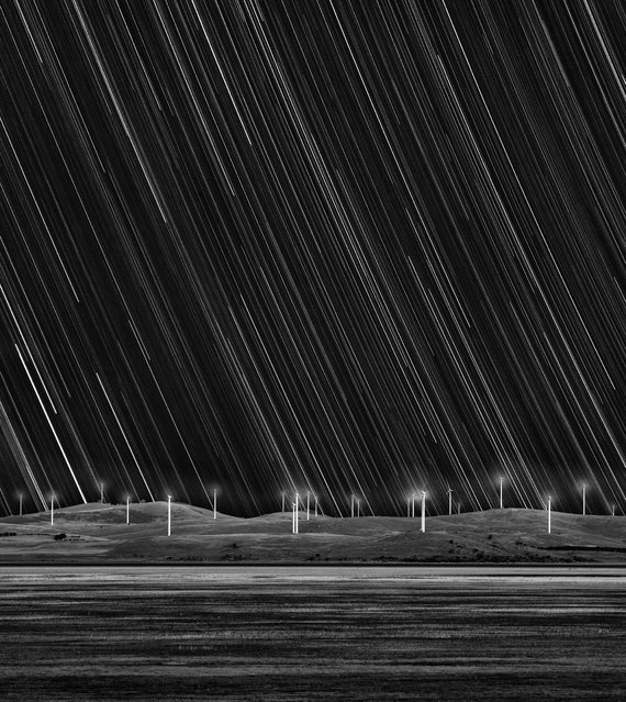"""Wind Farm Star Trails"". Taken in Australia near the town of Bungendore, this image captures the Capital Wind Farm on the shore of Lake George. The striking monochromatic compostion depicts the power of the wind along with the motion of the sky, illuminated by the shower of stars transforming into trails as the Earth rotates. Runner up in the Earth and Space category. (Photo by Matt James, Australia/The Astronomy Photographer of the Year 2014 Contest)"