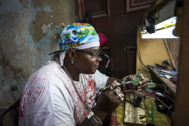 """Private jeweler and electronics technician Gabriel La O repairs a mobile phone inside a government store where he rents work space in Havana, Cuba, Tuesday, May 24, 2016. Cuba says it will legalize small and medium-sized private businesses by adding a category of small, mid-sized and """"micro"""" private business to the Communist party's master plan for social and economic development. The government currently allows private enterprise by self-employed workers in several hundred job categories. (Photo by Desmond Boylan/AP Photo)"""