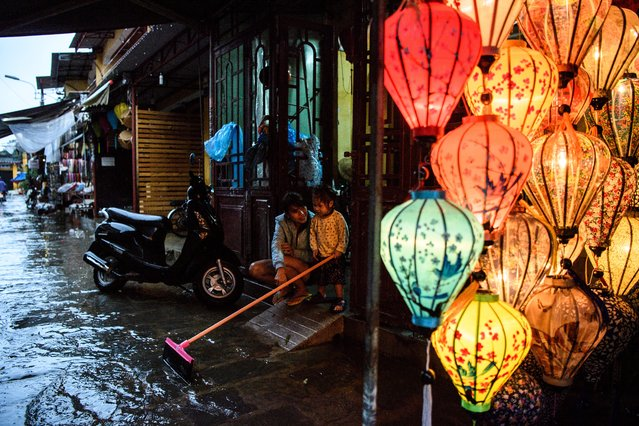 A mother and her child sit in their house entrance next to a lantern shop in the town of Hoi An on November 8, 2017 following days of heavy rains after Typhoon Damrey hit the coast. The death toll from typhoon downpours and floods wreaking havoc along Vietnam's south-central coast had risen to 69, authorities said on November 7, as the country prepares to host the world leaders' Asia-Pacific Economic Cooperation (APEC) Summit in Danang, just north of Hoi An. (Photo by Anthony Wallace/AFP Photo)