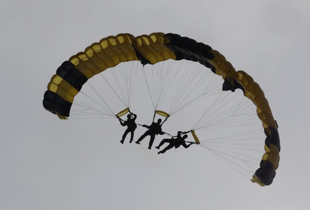 South Korean special army soldiers parachute down during the 66th anniversary of Armed Forces Day at the Gyeryong military headquarters in Gyeryong, South Korea, Wednesday, October 1, 2014. (Photo by Ahn Young-joon/AP Photo)