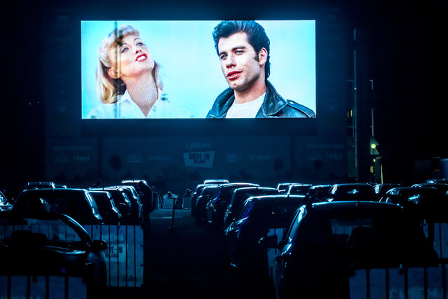 "People in their cars watch the film ""Grease"" with John Travolta and Olivia Newton-John at the opening of a new drive-in cinema in Milan on June 24, 2020 in Milan, Italy. (Photo by Francesco Prandoni/Getty Images)"