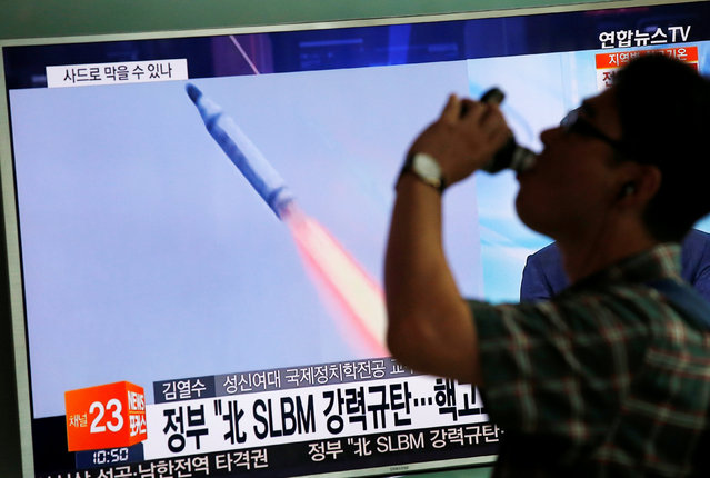A passenger walks past a TV screen broadcasting a news report on North Korea's submarine-launched ballistic missile fired from North Korea's east coast port of Sinpo, at a railway station in Seoul, South Korea, August 24, 2016. (Photo by Kim Hong-Ji/Reuters)