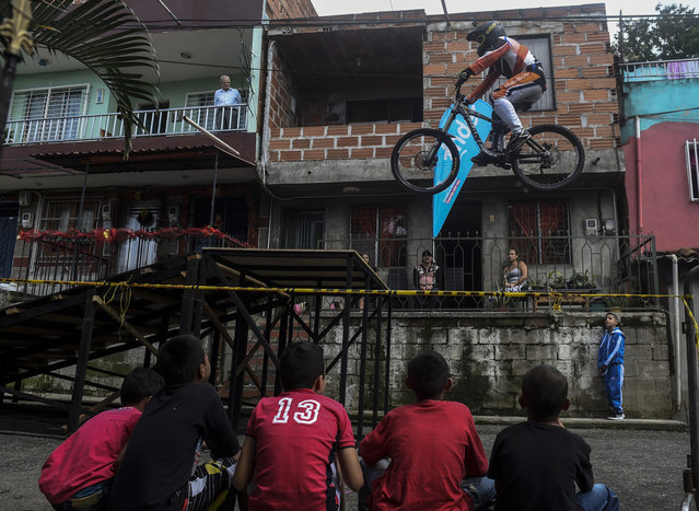 Residents looks at a downhill rider during the Urban Bike Inder Medellin race final at the Comuna 1 shantytown in Medellin, Antioquia department, Colombia on November 19, 2017. (Photo by Joaquin Sarmiento/AFP Photo)