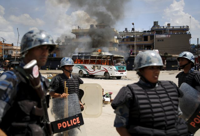 Members of Nepalese Armed Police Force stand in front of a burning passenger bus after it was set on fire by unidentified protesters during the nationwide strike, called by the opposition parties against the proposed constitution, in Kathmandu, Nepal September 20, 2015. (Photo by Navesh Chitrakar/Reuters)