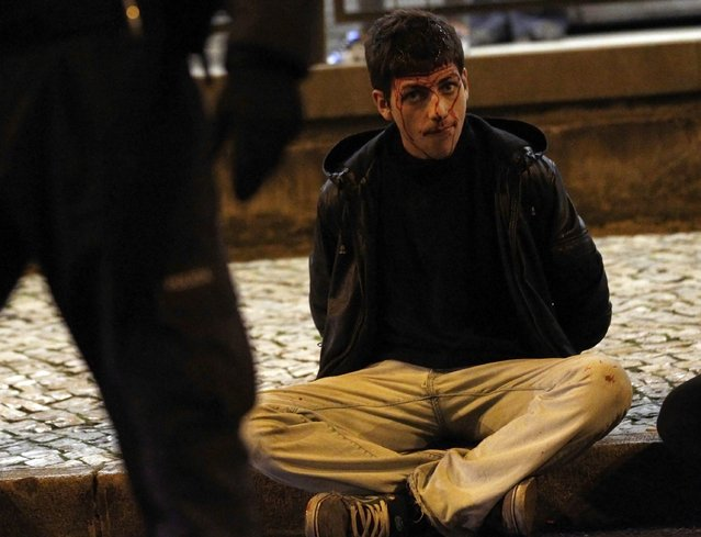 An injured protester sits in the street after being detained during clashes at a 24-hour nationwide general strike in Lisbon, November 14, 2012. Spanish and Portuguese workers will stage the first coordinated general strike across the Iberian Peninsula on Wednesday, shutting transport, grounding flights and closing schools to protest against spending cuts and tax hikes. (Photo by Rafael Marchante/Reuters)