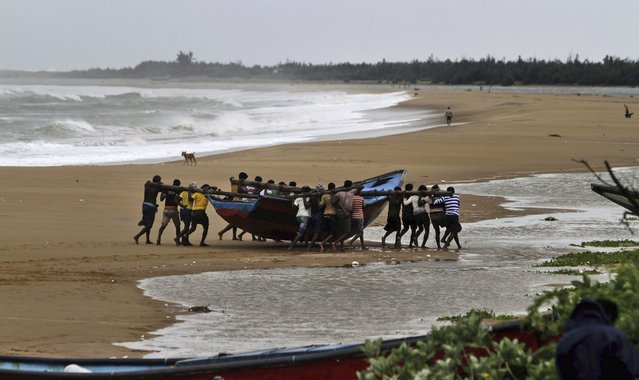 Indian fishermen move a boat away from the coast following a cyclone warning near Podampeta village, on the outskirts of Gopalpur beach in Ganjam district, 140 kilometers (87 miles) south of Bhubaneswar, India, Saturday, October 11, 2014. (Photo by Biswaranjan Rout/AP Photo)