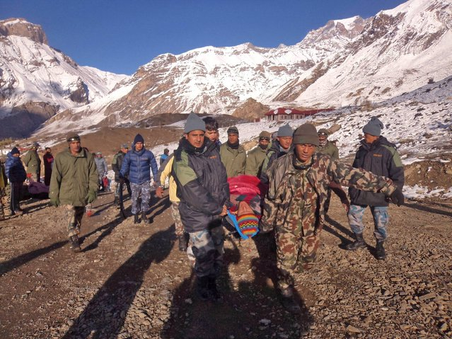 In this photo provided by the Nepalese army, soldiers carry an avalanche victim before he is airlifted in Thorong La pass area, Nepal, Wednesday, October 15, 2014. An avalanche and blizzard in Nepal's mountainous north have killed at least 12 people, including eight foreign trekkers, officials said Wednesday. Five other climbers were hit by a separate avalanche on Mount Dhaulagiri and remain missing. (Photo by AP Photo/Nepalese Army)
