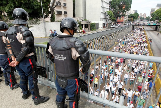 Police officers look on as opposition supporters take part in a rally to demand a referendum to remove Venezuela's President Nicolas Maduro in Caracas, Venezuela, September 1, 2016. (Photo by Christian Veron/Reuters)