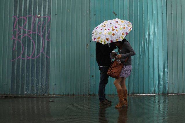 A couple shelters under an umbrella as it rains in downtown Mexico City October 2, 2014. (Photo by Tomas Bravo/Reuters)