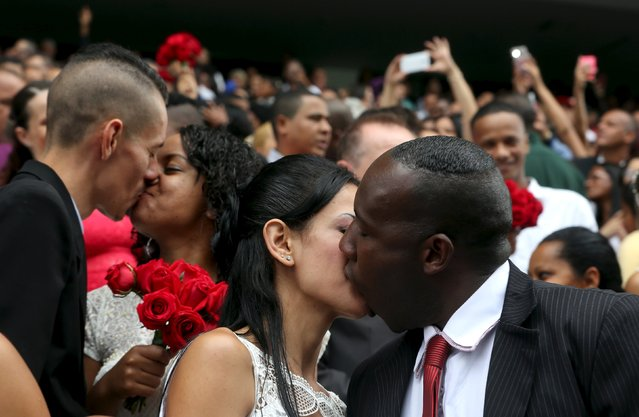 Newlywed couples kiss during a mass wedding ceremony at Arena Corinthians soccer stadium in Sao Paulo, Brazil, September 26, 2015. (Photo by Paulo Whitaker/Reuters)