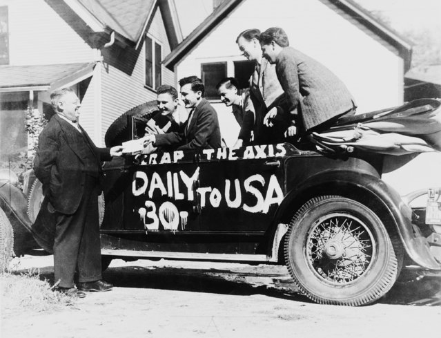 """Five University of Michigan editors, co-owners of a 1929 auto, bring the car to George H. Gabler, left, Washtenaw County scrap chairman at Ann Arbor, Michigan on October 10, 1942, and ask him to """"send it to war"""". The aged vehicle weighs 4,250 pounds and has six """"middle-aged"""" 7x20 tires. The owners, all staff members of the Michigan """"Daily"""", are from left to right: Harry Levine, Brooklyn, N.Y.; Homer Swandlers, Kalamazoo, Mich.; Hale Champion, Ann Arbor; Ed Perlberg, Standish, Mich.; and Myron Dann, Detroit. (Photo by AP Photo)"""