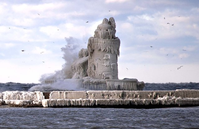 This image provided by the U.S. Coast Guard shows waves from Lake Erie crash onto the Cleveland Harbor West Pierhead Lighthouse on Tuesday, as the subzero air temperature caused the water to freeze in multiple layers, coating the entire structure in ice and making it virtually impossible for mariners to see the light. (Photo by Petty Officer 2nd Class Lauren Jorgensen U.S. Coast Guard/Associated Press)