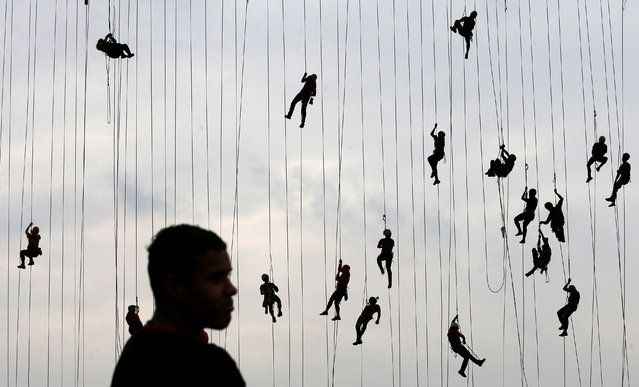 """People climb after jumping off a bridge, which has a height of 30 meters, in Hortolandia, Brazil, October 22, 2017. According to organizers, 245 people were attempting set a new world record for """"rope jumping"""", in which people, tied to a safety cord, jump off a bridge. (Photo by Paulo Whitaker/Reuters)"""