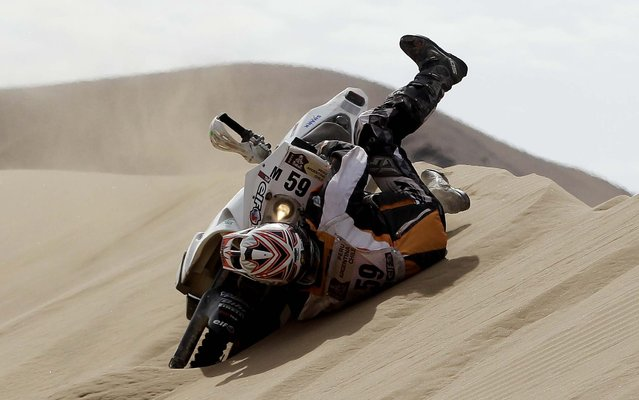 KTM rider Patrice Carillon of France falls from his motorcycle as he tries to cross a dune during the 6th stage. (Photo by Victor R. Caivano/Associated Press)