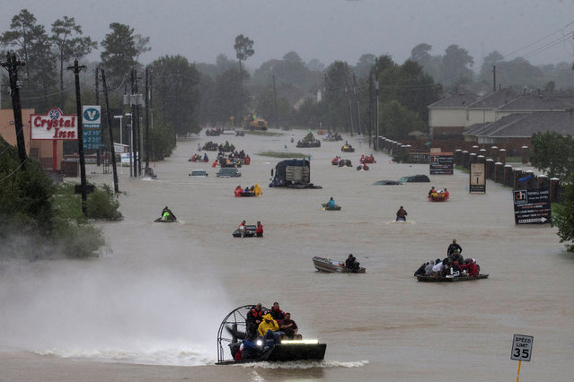 Residents use boats to evacuate flood waters from Tropical Storm Harvey along Tidwell Road, east Houston, Texas, August 28, 2017. (Photo by Adrees Latif/Reuters)