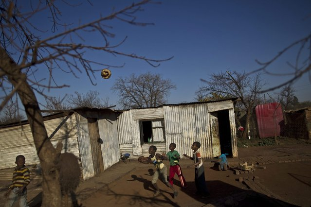 South African children play football with a torn ball in a yard in a Soweto township on the outskirts of Johannesburg, South Africa, Wednesday, July 3, 2013. (Photo by Muhammed Muheisen/AP Photo)