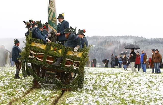 Farmers dressed in traditional Bavarian costumes ride in a wooden carriage on the way to the chapel on the Kalvarienberg in Bad Toelz, during the Leonhard procession November 6, 2014. The Leonhardi Ritt procession is an annual event that started in the 17th century to pray to St. Leonhard, the patron saint of animals. (Photo by Michaela Rehle/Reuters)