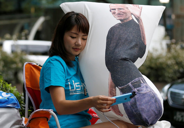 Ayano Tominaga holds a cushion printed a portrait of Apple co-founder Steve Jobs on it, as she sits in queue for the release of Apple's new iPhone 7 and 7 Plus in front of the Apple Store in Tokyo's Omotesando shopping district, Japan, September 16, 2016. (Photo by Issei Kato/Reuters)