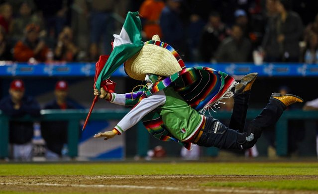 """A Mexican baseball fan, who identified himself as """"El Pony de Nogales"""", slides at home plate after jumping on to the field in the ninth inning of the game between Mexico and Puerto Rico during the Caribbean Baseball Series in Hermosillo, on February 7, 2013. Mexico won 10–0 and will play for the championship against the Dominican Republic. (Photo by Andres Leighton/Associated Press)"""