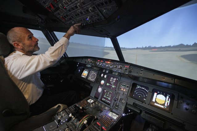 Igor Perne (R), 53, an electronic engineer and a member of the International Virtual Aviation Organisation (IVAO), checks the controls after landing a virtual flight in a flight simulator in Nova Vas November 13, 2014. (Photo by Srdjan Zivulovic/Reuters)