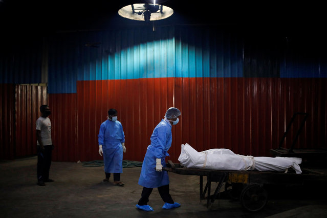 A health worker wearing personal protective equipment (PPE) carries the body of a man, who died due to the coronavirus disease (COVID-19), at a crematorium in New Delhi, India on September 7, 2020. (Photo by Adnan Abidi/Reuters)