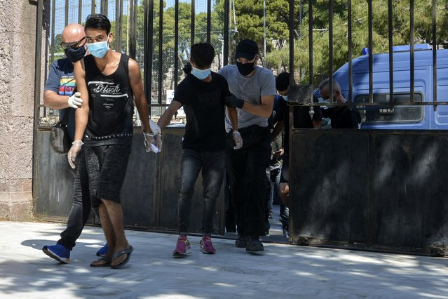 Suspects, all from Afghanistan escorted by plain clothes policemen and wearing face masks, arrive at a court in Mytilene, the capital of the northeastern Aegean island of Lesbos, Greece, Wednesday, September 16, 2020. The government says the fires in Moria refugee camp were set deliberately by the Afghan migrants protesting a coronavirus lockdown, and authorities on Tuesday announced the arrests of six suspect, include two 17-year-olds, in the case. (Photo by Panagiotis Balaskas/AP Photo)