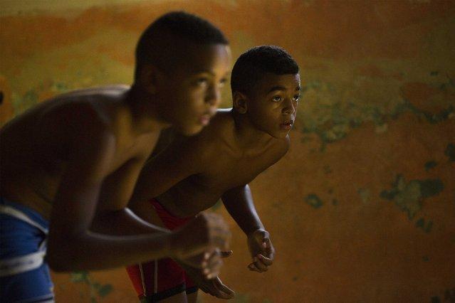 Children practice wrestling in downtown Havana, October 30, 2014. (Photo by Alexandre Meneghini/Reuters)