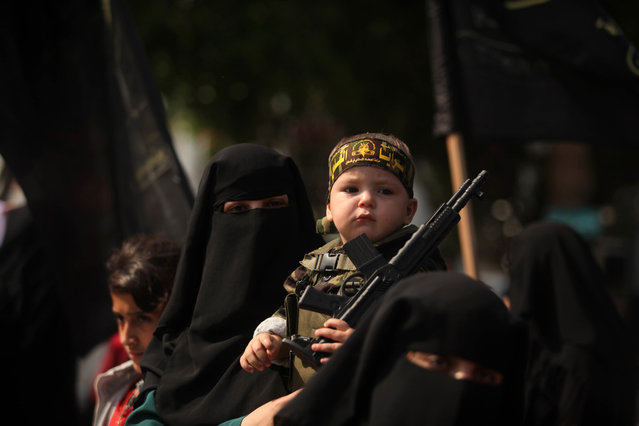 A Palestinian woman supporting the Islamic jihad movement holds her son during a rally in Gaza City, Palestine on October 19, 2015. (Photo by Majdi Fathi/NurPhoto/Corbis)