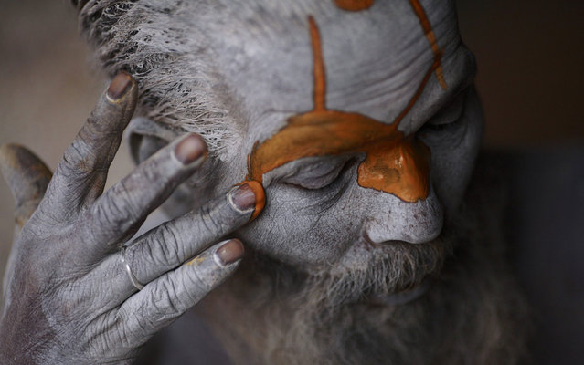 A ascetic, wandering monk (Sadhu) prepares itself for ritual in Pashupatinath temple, to Kathmandu, Nepal, on March 4, 2013. (Photo by Navesh Chitrakar/Reuters)