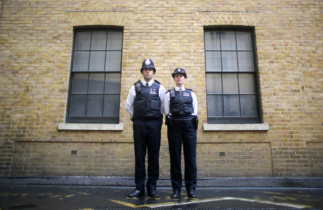 "Police constables Ben Sinclair and Karen Spencer pose for a photograph wearing their Metropolitan Police beat uniforms, in London, October 9, 2014. In Britain, ""lethal or potentially lethal force should only be used when absolutely necessary in self-defence, or in the defence of others against the threat of death or serious injury"". (Photo by Paul Hackett/Reuters)"